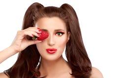Glückliches Mädchen mit Erdbeere im Auge und im lustigen Ausdruck Stockfoto
