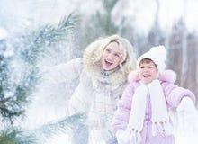 Glückliches mopther und Kind, die mit Schnee im Winter spielt Stockfoto