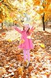 Glückliches nettes kleines Mädchen, das mit Ahornblättern spielt Stockfoto