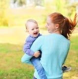 Glückliches nettes lächelndes Mutter- und Sohnkind, das Spaß draußen hat Stockfoto