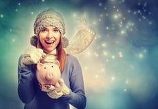 Glückliches niederlegendes Geld der jungen Frau in ihr Sparschwein Lizenzfreies Stockbild