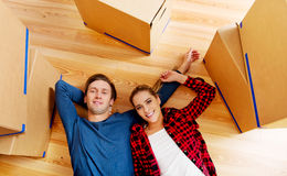 Glückliches Paar, das auf dem Boden im neuen Haus mit cordboard Kästen herum liegt Lizenzfreies Stockfoto