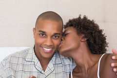Glückliches Paar, das auf dem streichelnden Bett sitzt Lizenzfreies Stockfoto