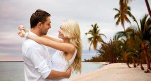 Glückliches Paar, das über Strandhintergrund umarmt Stockbilder