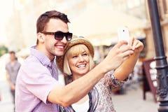 Glückliches Paar, das ein Foto von selbst bei der Besichtigung macht Stockbild