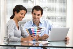 Glückliches Paar, das Farben beschließt, um neues Haus zu malen Lizenzfreie Stockfotografie