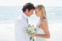 Glückliches Paar, das an ihrem Hochzeitstag sich umfasst Stockbild