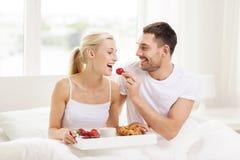 Glückliches Paar, das im Bett zu Hause frühstückt Stockbild