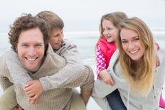 Glückliches Paar, das Kinder am Strand huckepack trägt Lizenzfreie Stockbilder