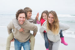 Glückliches Paar, das Kinder am Strand huckepack trägt Stockfotos