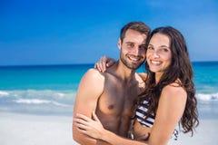 Glückliches Paar, das am Strand umfasst und Kamera betrachtet Stockfotos