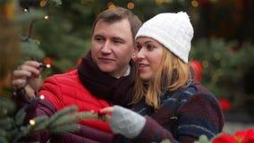 Glückliches Paar, das Weihnachtsbaum an Weihnachtsmesse wählt Junge Familie, die auf dem Weihnachtsmarkt spricht und küsst fröhli stock video