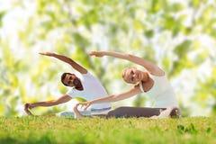 Glückliches Paar, das Yogaübungen ausdehnt und tut Stockbild