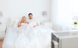 Glückliches Paar, das zu Hause im Bett und in aufpassendem Fernsehen liegt Stockbilder