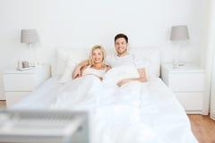 Glückliches Paar, das zu Hause im Bett und in aufpassendem Fernsehen liegt Stockfoto
