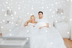 Glückliches Paar, das zu Hause im Bett und in aufpassendem Fernsehen liegt Stockfotografie