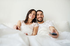 Glückliches Paar, das zu Hause im Bett und in aufpassendem Fernsehen liegt Stockfotos