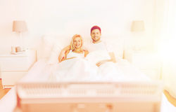 Glückliches Paar, das zu Hause im Bett und in aufpassendem Fernsehen liegt Stockbild