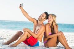Glückliches Paar, das zurück zu Rückseite auf Strand sitzt Stockfotografie