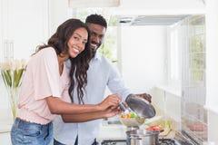Glückliches Paar, das zusammen Lebensmittel kocht Stockfotos