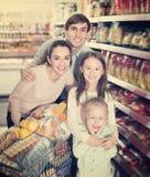 Glückliches Paar mit dem Einkauf mit zwei Töchtern Lizenzfreie Stockfotografie