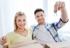 Glückliches Paar mit Schlüssel und Kästen, die auf neues Haus sich bewegen Lizenzfreies Stockfoto