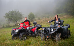 Glückliches Paar, welches die vierrädrige Droschke ATV nicht für den Straßenverkehr fährt Lizenzfreies Stockbild
