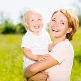 Glückliches Porträt des Mutter- und Kleinkindsohns im Freien Lizenzfreies Stockfoto