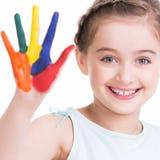 Glückliches recht kleines Mädchen mit den gemalten Händen Stockfoto