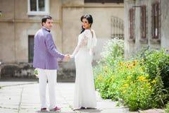 Glückliches schönes Paar-, Braut- und Bräutigamhändchenhalten in einem stree Lizenzfreie Stockfotos