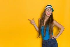 Glückliches Sommer-Mädchen, das auf gelbe Wand zeigt Stockbild