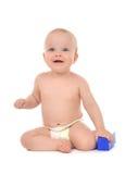 Glückliches Säuglingskinderbabykleinkind, das mit blauem Spielzeugziegelstein sitzt Lizenzfreie Stockfotos