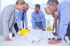 Glückliches Team von den Geschäftsleuten, die über Bauplan sprechen Lizenzfreies Stockbild