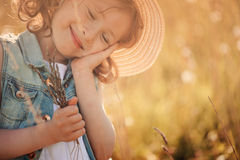 Glückliches träumendes Kindermädchen, das Blumenstrauß im Sommer hält Stockfotos