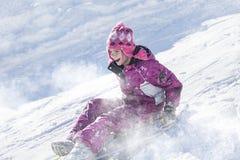 Glückliches und aufgeregtes Mädchen, das abwärts an einem schneebedeckten Tag rodelt Stockfotografie