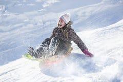 Glückliches und aufgeregtes Mädchen, das abwärts an einem schneebedeckten Tag rodelt Lizenzfreie Stockfotografie