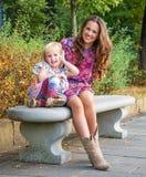 Glückliches Unterhaltungsmobiltelefon der Mutter und der Tochter am Park Stockfotografie