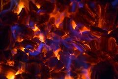 Glödande glöd med blåa flammor Arkivbilder