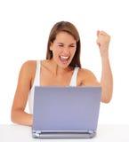 Glädjande kvinna med bärbar dator Royaltyfria Bilder