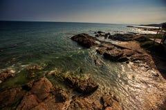 Gleam das ondas do mar de turquesa sob a luz solar que lava Rocky Beach imagem de stock royalty free