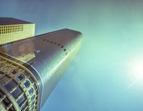 Gleaming skyscraper with bright sun blue sky background Royalty Free Stock Photography