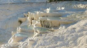 Gleaming white calcite shelves of Pamukkale. Overrunning with warm mineral-rich waters and the adjacent ruins of Hierapolis on the top of the hill Royalty Free Stock Photos