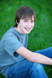 Gleeful. Handsome teen guy model seated in grass smiling Stock Photo