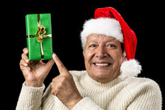 Gleeful Aged Man Pointing At Raised Green Present. Light-hearted male senior with a red Father Christmas cap cracking a smile. He is pointing at a long, green Royalty Free Stock Photo