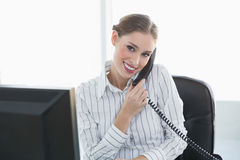 Gleeful chic businesswoman phoning with telephone sitting at her desk Stock Photo