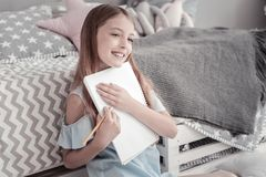 Gleeful girl hugging her notebook royalty free stock photo