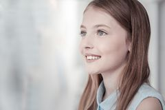 Gleeful pretty girl smiling and thinking royalty free stock photo
