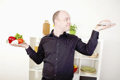 Man making a choice on food and diet. Gleeful smiling man standing in his kitchen with his arms raised with two plates, one with fresh vegetables and one with Stock Image