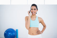 Gleeful sporty woman phoning while standing in fitness hall Stock Image