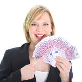 Gleeful woman pointing to bunch of 500 euro notes. Gleeful young woman pointing to a fistful of 500 euro notes which she is holding fanned in her hand isolated Royalty Free Stock Images